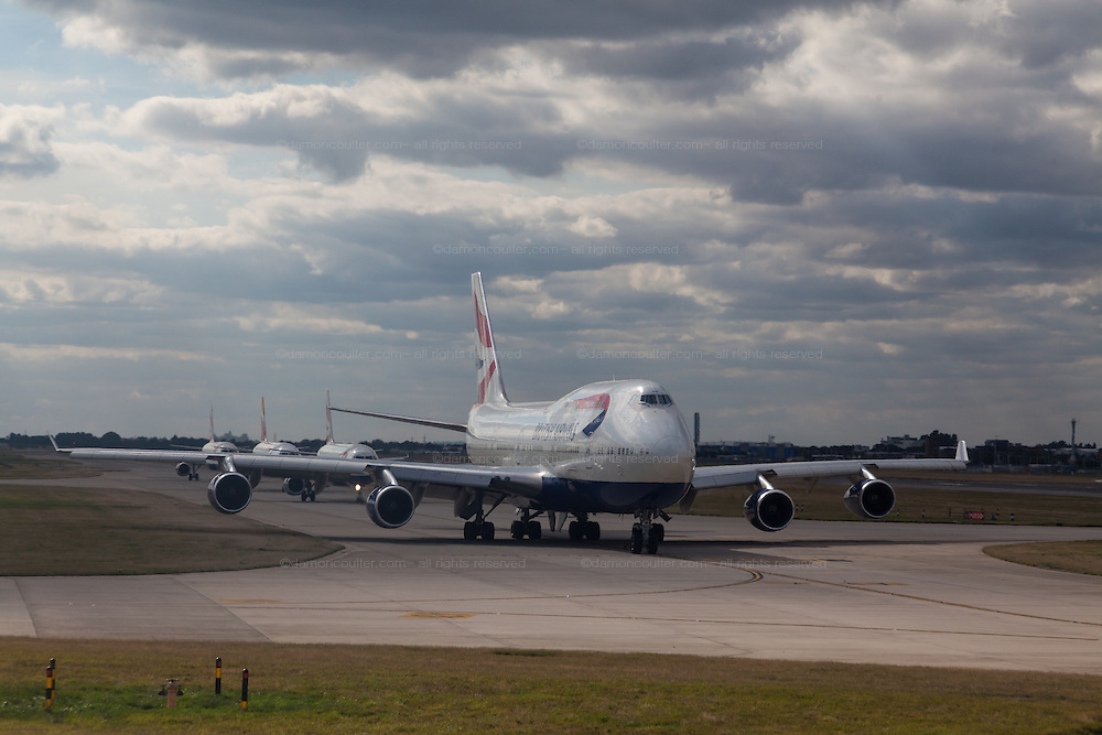 A Boeing 747 airliner (Jumbo jet) belonging to British Airways lines up on a taxi-way with other airliners before taking off from Heathrow Airport, London, UK Sunday August 17th 2014