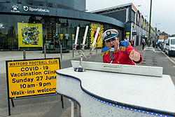 """© Licensed to London News Pictures. 27/06/2021. WATFORD, UK. A man dressed as Elton John, a lifelong Watford supporter, rides round on a mobile piano entertaining people arriving to receive a first dose of the Pfizer vaccine at a pop-up mass vaccination clinic at Watford FC's Vicarage Road Stadium as part of the """"Grab a jab"""" campaign. The NHS is also promoting a number of walk-in clinics this weekend across the capital to try to increase the number of over 18s receiving a jab as cases of the Delta variant are reported to be on the rise..  Photo credit: Stephen Chung/LNP"""