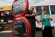 Spectators take recently-purchased food away past a menu and price sign in the Olympic Park during the London 2012 Olympics. This land was transformed to become a 2.5 Sq Km sporting complex, once industrial businesses and now the venue of eight venues including the main arena, Aquatics Centre and Velodrome plus the athletes' Olympic Village. After the Olympics, the park is to be known as Queen Elizabeth Olympic Park.