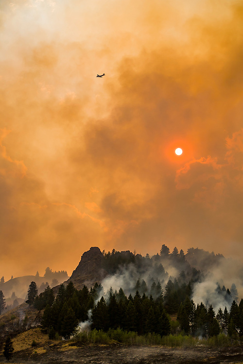 Raging fire moves like a living beast just north of Ketchum Idaho with the sun burning through the smokey clouds as trees go up in flames. Licensing and Open Edition Prints.