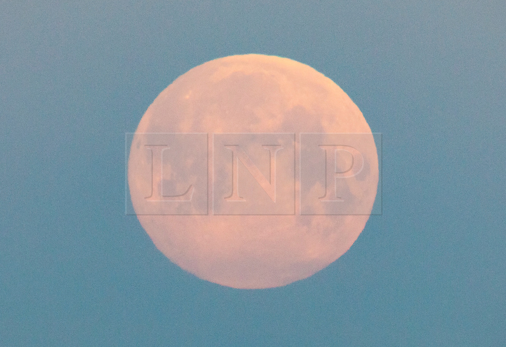 © Licensed to London News Pictures. 07/05/2020. London, UK. The near full supermoon sets over a misty London. Also know as the Flower Moon at this time of year - it will be at it's fullest as it rises later tomorrow. A supermoon is a full or new moon that comes closest to the Earth in its elliptical orbit—resulting in a slightly larger than usual apparent size when viewed from Earth. Photo credit: Peter Macdiarmid/LNP