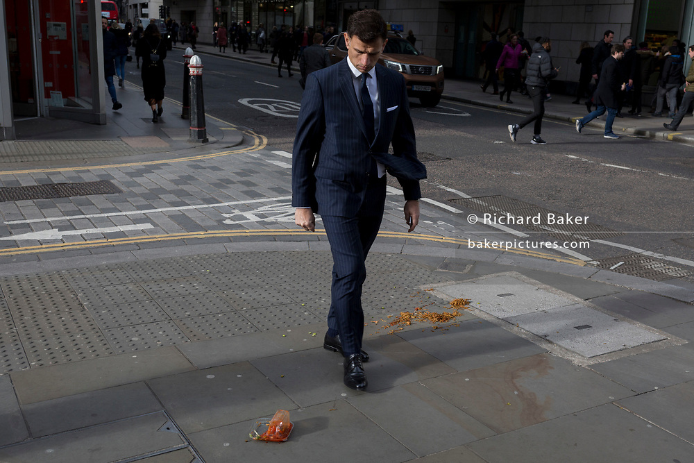 Pedestrians avoid a noodle and sauce takeaway, dropped and discarded on the pavement during lunch-hour in the capital's financial district, on 4th February 2020, in the City of London, England. The lunchtime meal was being carried along the street when its heat and moisture made it drop through the bottom of a paper bag, turning it upside down and lying perfectly on the pavement as city workers emerged from their offices. Those who saw it in time stepped over the greasy obstacle but the distracted (mostly by walking with phones to ears), stepped in it and helping spread it across the pavement.