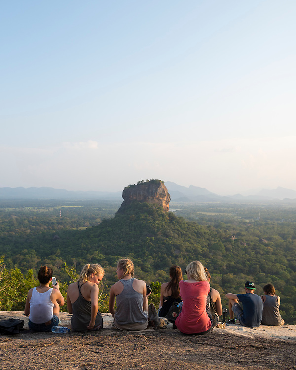 After hiking to the top of Pidurangala Rock, young adult travelers visiting Sri Lanka enjoy the view of the famous Sigiriya rock fortress.