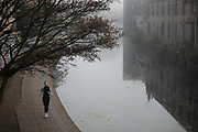 A runner makes her way along the Regents Canal on a misty morning, 27th of November 2020, Hackney, London, United Kingdom. The towpath along the canal is a popular route for runners, dog walkers and people in general.
