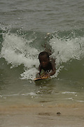 Antandroy child body-surfing in the waves with home-made boogie board made from wood.  Lavanono fishing village, south coast of MADAGASCAR