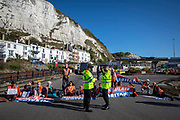 Activists from Insulate Britain blockade the entrance to the port of Dover on the 24th of September 2021 in Dover, United Kingdom. Over 40 activists from Insulate Britain blocked the road with some gluing themselves to the carriageway of the A20 at the Eastern docks roundabout. There are blocking the roads to highlight that fuel poverty is killing people in Dover and across the UK.