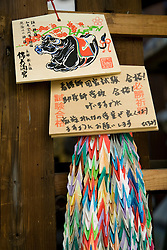 Asia, Japan, Honshu island, Kyoto, origami strands and wooden prayer plaques at Nishiki Tenman-gu Shrine