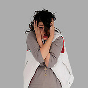 exaggerated and comic look at a young frightened woman hugging herself in fear studio shot on white background