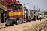 ROYAL CAMBODIAN RAILWAYS. The journey from Phnom Penh to Battambang is the last working route. A passenger train, operates only at weekends. A Czech made diesel locomotive, leaves the capital Saturday morning, arriving in Battambang 22 hours later in the dead of night, and returns on Sunday. Max speed is about 30kmh, often slower due to the track's terrible condition. Carriages are dilapidated, with holes in the floor and only spaces for windows. Passengers sit or sleep on hardwood bench seats, hammocks, or on the floor of cargo carriages. The drivers, controllers & guards add to their small monthly pay by charging for local passengers and cargo; from motor bikes and local produce to timber loaded aboard at the 30 stations along the route. This together with other trains and farm vehicles further slows the journey. In rural areas, the track is a lifeline, and used for local transport on 'bamboo trains' powered by belt-motors, or pushcarts. Boom towns, with a 'goldrush mentality' near the rapidly depleted rainforest, are a hive of activity, with logging as their resource, where children workers even gamble away their earnings on cardgames. In the city, the railway has a life of its own, where people live and work nearby or on the track itself. Market stalls, restaurants, chairs and tables, are removed only briefly, when the infrequent train passes!///Czech train stopped in Pursat Station