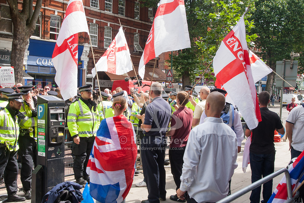 """Cricklewood, London, July 19th 2014. A handful of protesters from the anti-Islamist """"South East Alliance"""" protest outside the London office of Egypt's Muslim Brotherhood, as large numbers of police keep them and counter-protesting anti-fascists separate."""