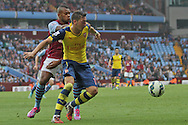 Mesut Ozil of Arsenal holds off Leandro Bacuna of Aston Villa. Barclays Premier league match, Aston Villa v Arsenal at Villa Park in Birmingham on Saturday 20th Sept 2014<br /> pic by Mark Hawkins, Andrew Orchard sports photography.
