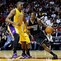 19 January 2012:  Miami Heat point guard Mario Chalmers (15) drives past Los Angeles Lakers center Andrew Bynum (17) during the Miami Heat 98-87 victory over the Los Angeles Lakers at the AmericanAirlines Arena, Miami, Florida, USA.