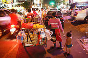 At nightime, Pi, a young girl helps her parents scavenging for plastic, metal and cardboard on the city streets. Recycling workers, Phnom Penh. Rural peasants who have left the countryside in search of earning a decent living often end up as recycling workers on Phnom Penh's city streets. They earn a few dollars a day from selling by weight the plastic bottles, aluminium cans and cardboard they collect during a days work. Usually they work from the mid afternoon until midnight, sorting through the rubbish on the streets. They take what they collect to small sorting houses on the edge of the city.