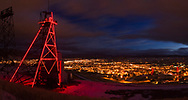 Mining gallows frames lit up at night signify the historic mining at Butte, Montana, USA