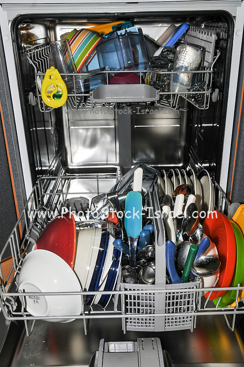 Dish washer stacked with dishes, cups and cutlery