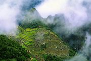 Machu Picchu, Peru, storm clouds and mist. A major tourist attraction.