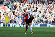 Fulham's Konstantinos Mitroglou ® is challenged by Cardiff's Steven Caulker. Barclays Premier league, Cardiff city v Fulham at the Cardiff city Stadium in Cardiff , South Wales on Sat 8th March 2014. pic by Andrew Orchard, Andrew Orchard sports photography