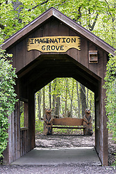 Small covered bridge spanning the Sugar Creek and a hand carved bench are both found in the Sugar Grove Nature Center near Funks Grove