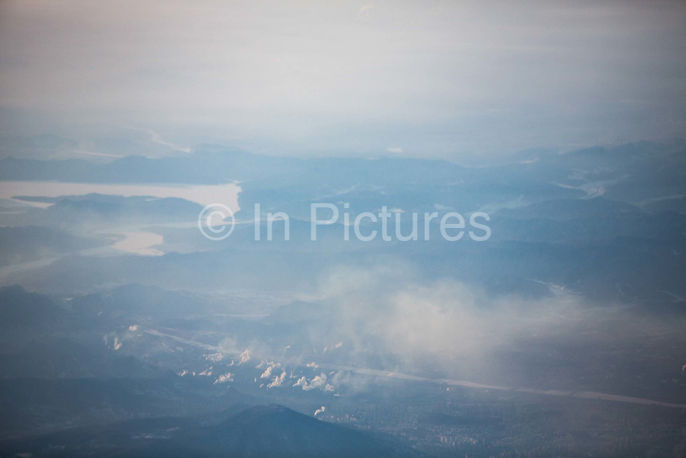 Seen from the air, smoke and exhaust rises up from power plants and other industrial complexes above a snow covered Tonghua, Jilin Province, China on 05 January 2018.