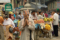 Devout Hindu man preys while walking through a colourful market in Indra Chawk Square of Kathmandu, Nepal.