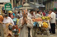 Devout Hindu man preys while walking through a colourful market in Indra Chawk Square of Kathmandu, Nepal.