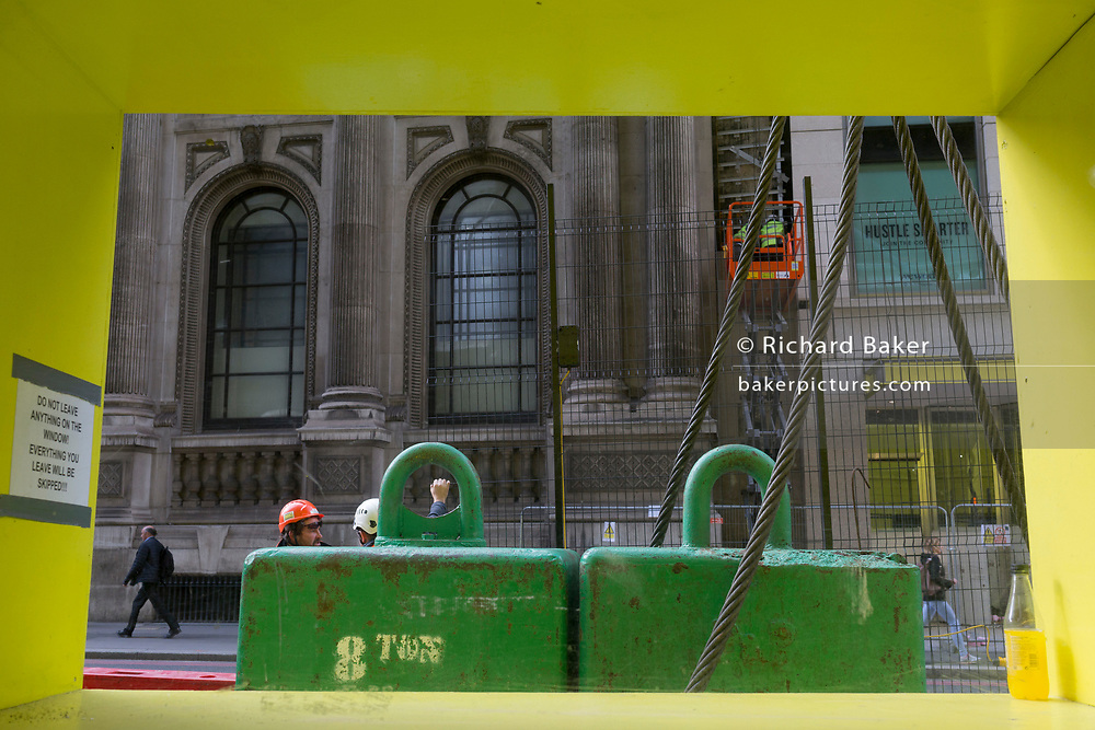 Construction workmen supervise the lifting of materials, seen through a rectangular yellow site window, on 14th September 2017, in the City of London, England.