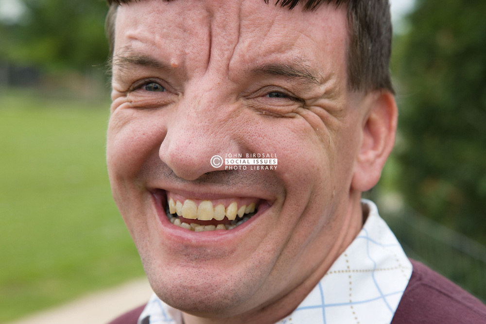 Portrait of a man with learning disabilities smiling,