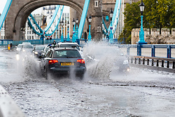 © Licensed to London News Pictures. 06/10/2019. London, UK. Traffic drives through flooding and excess surface water on Tower Bridge this morning following heavy rain and wet weather in the capital last night. Weather forecasts predict that most of the UK will be experience heavy rain and storms during the next few days. Photo credit: Vickie Flores/LNP