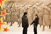 Moscow, Russia, 05/11/2005..A young woman pleads with a policeman checking her documents on Red Square in front of decorations erected for a military parade on November 7 to commenorate a similar parade during World War Two when soldiers left for the front.