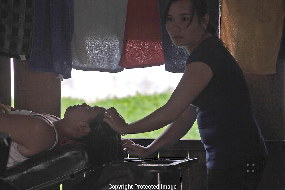 A lady gets a shampoo in the town of Phong Nam Village. Photograph by Dennis Brack
