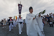 A shinto priest blesses the Mikoshi during the Hamaorisai matsuri in Chigasaki, Kanagawa, Japan. Monday July 17th 2017.  This festival is celebrated on Marine Day in Japan. Over 40 mikoshi (portable shrines) are paraded through the night to arrive on the coast at Southern Beach where they are blessed in a Shinti ritual before being carried into the waves to be purified.