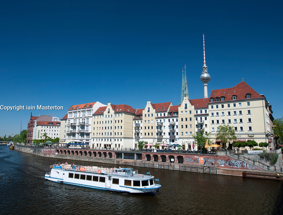 Tourist river tour boat passes historic Nikolaiviertel district of Berlin Germany