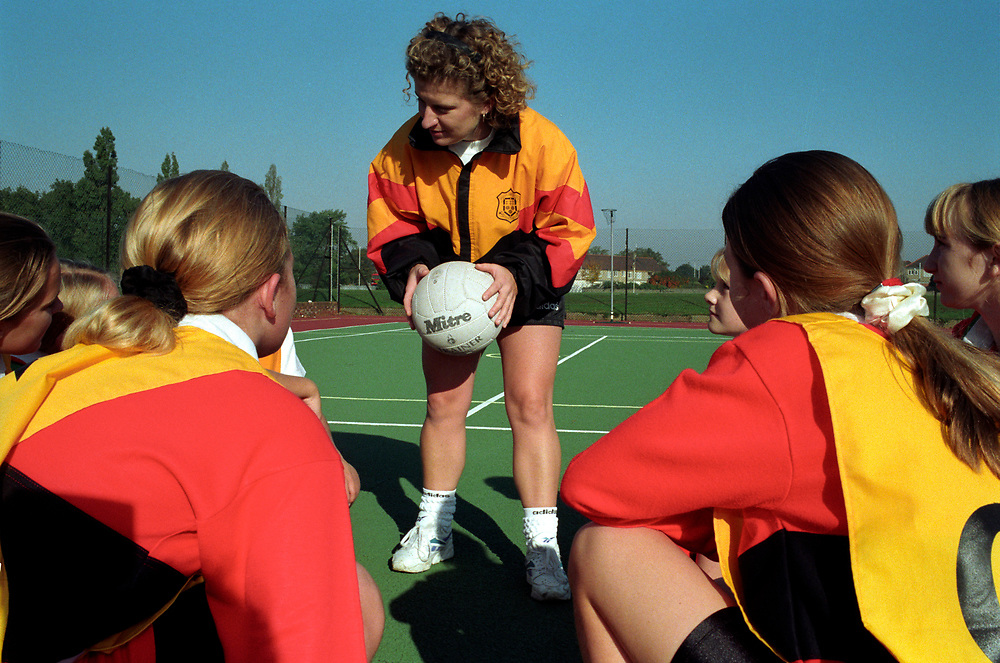 Females playing basket/netball  at a secondary school,