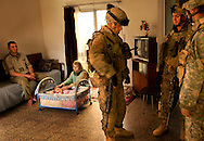 An Iraqi mother tends to her baby as soldiers stand in her house looking for weapons.