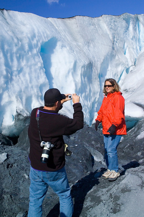A couple take pictures of eachother next to the face of Matanuska Glacier in the Matanuska Valley