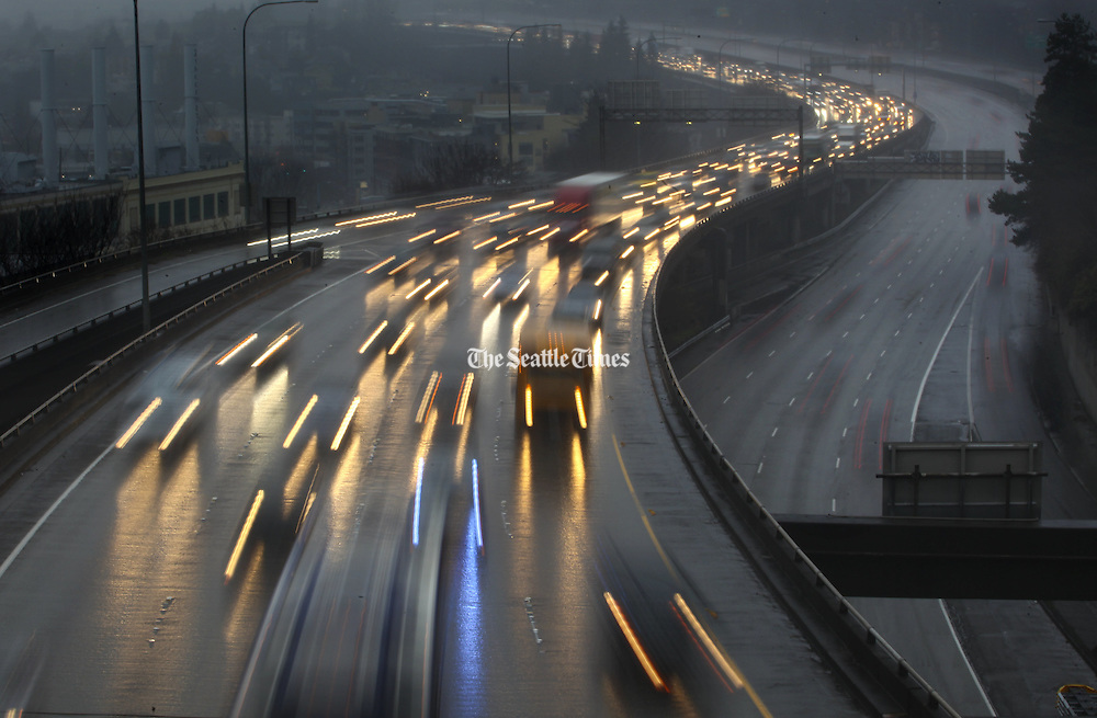Headlights reflect on the wet roadway as heavy traffic kicks up a lot of water as showers continue one afternoon in Seattle.  Looking north near the overpass that crosses I-5 at Belmont Ave. E. in Seattle. (Ellen M. Banner / The Seattle Times)