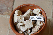 Plant pot with soil sample to illustrate different soil types, part of a series: calcareous calcium carbonate rock, calcaire. Chateau Villerambert-Julien near Caunes-Minervois. Minervois. Languedoc. Terroir soil. France. Europe. Calcareous limestone.