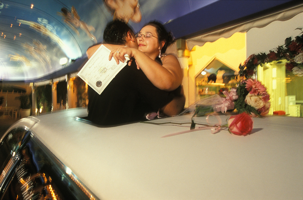 A happy couple embracing each other after just having been married at a drive-thru wedding at A Little White Wedding Chapel in Las Vegas, Nevada, USA. They are standing in the sunroof of a rented Limousine and the bride is holding the marriage certificate. They groom is an immigrant from Nepal. The wedding industry is the third largest in Las Vegas after gambling and entertainment.