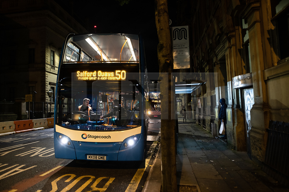 """© Licensed to London News Pictures. 10/10/2020. Manchester, UK. A number 50 bus to Salford Quays reminding passengers to """" Please wear a face covering """" on its electronic display . People out in pubs, bars and restaurants in Manchester City Centre ahead of the currently imposed daily 10pm curfew . Millions of people across the north of England are waiting to learn if the British Government will impose a regional lockdown on Monday (12th October 2020), as Coronovirus infection rates continue to rise rapidly . Photo credit: Joel Goodman/LNP"""