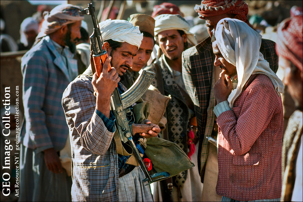 At a gun market in the northern province of Sadah near the Yemen-Saudi Arabia border, Yemeni tribesmen examine an AK-47 Kalashnikov assault rifle with a collapsible stock. The Sadah market offers supplies Arabian tribes with everything from hand grenades  and grenade launchers to machine guns, antitank mines, and even anti-aircraft weapons.