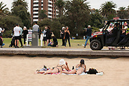 A small group of anti-lockdown protesters gather on St Kilda beach foreshore as beach goers and police watch on. After over 3 months of covid-19 lockdowns in Melbourne the easing of restrictions, allowed a small group of protesters to gather on St Kilda beach to protest police handing of demonstrations during the lock down. (Photo by Michael Currie/Speed Media)