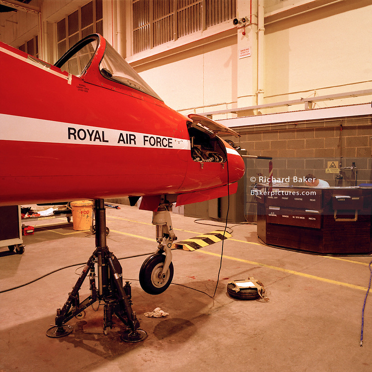 Scheduled maintenance on a Hawk jet in the hangar of the Red Arrows, Britain's RAF aerobatic team.