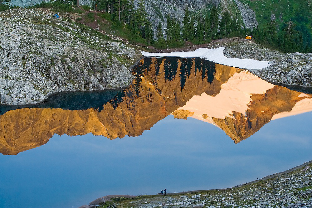 Hikers stand on the shore of Lake Ann, and the reflection of Mount Shuksan, in Mount Baker-Snoqualmie National Forest, Washington.
