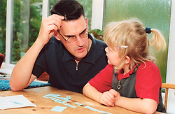 Father helping daughter with literacy skills UK MR