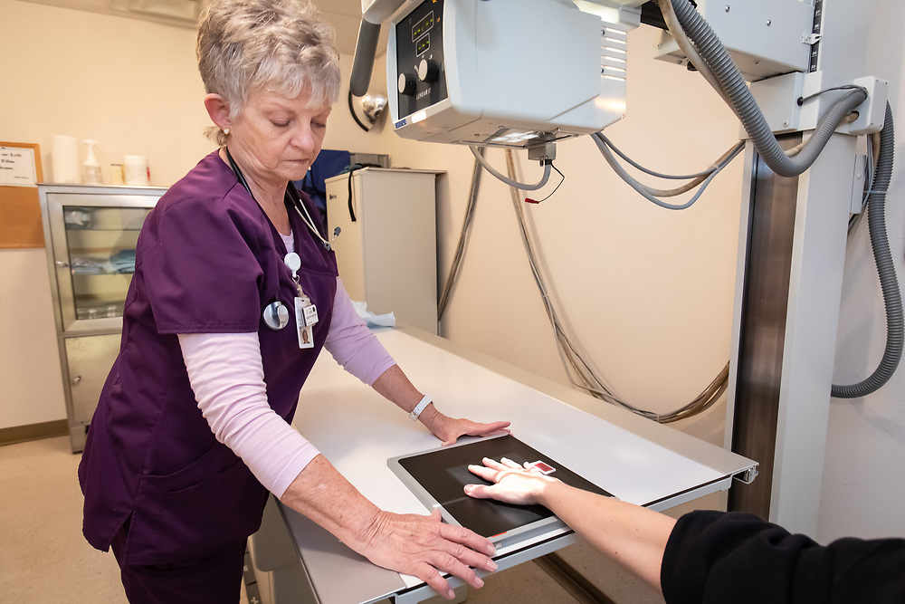 Licensed practical nurse and x-ray technician Ginger Ferron positions imaging equipment in Custer County Medical Center's x-ray facility.