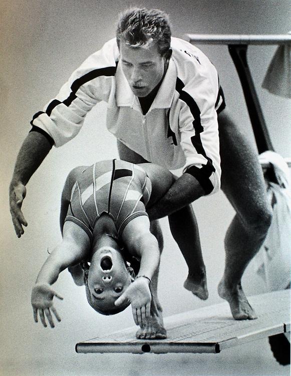 Diving coach Doug Shaffer helps a little girl perform a backward dive.