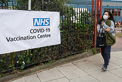 © Licensed to London News Pictures. 19/06/2021. London, UK. A woman leaves Bridge Park Community Centre in Brent. Hundreds of adults over 18 year old queue outside Bridge Park Community Centre in Brent to receive a Covid vaccination. People had been queuing since 08:00am with up to 2,700 vaccinations available. The event is part of a mass vaccination drive as UK scientists have commented on signs of a third Covid wave underway due to the B.1.617.2 strain or Delta variant of Covid. Photo credit: Ray Tang/LNP