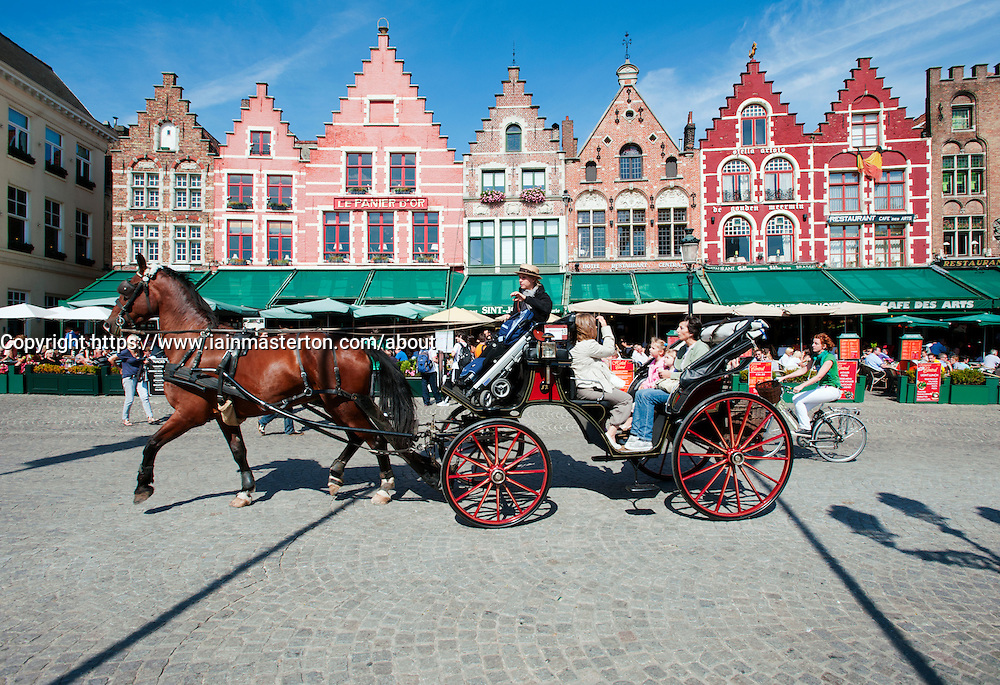 Horse and carriage city tour passes in front of row of ornate historic buildings and restaurants  in Market Square in Bruges in Belgium