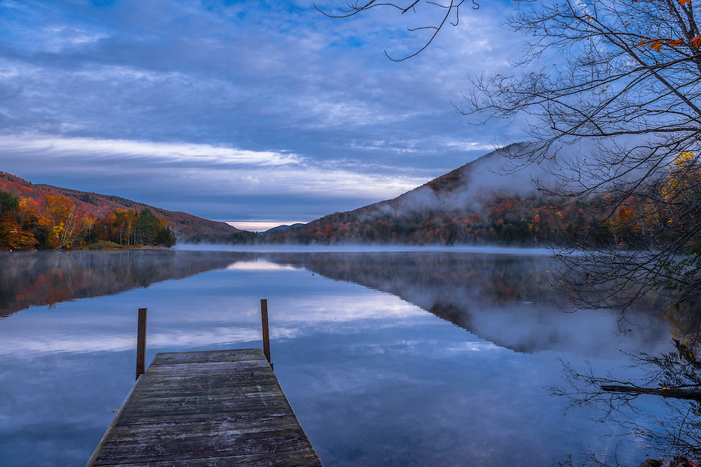 Wooden dock leads out into Woodward Reservoir, with fall foliage on mountains and fog, Plymouth, VT