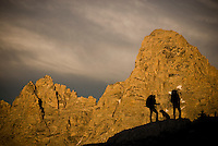 The Grand Teton looms behind two hikers in the high alpine of the Teton Range, Wyoming.